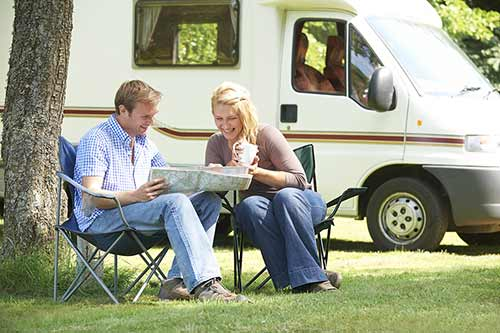 A couple sitting outside by their campervan reading a map