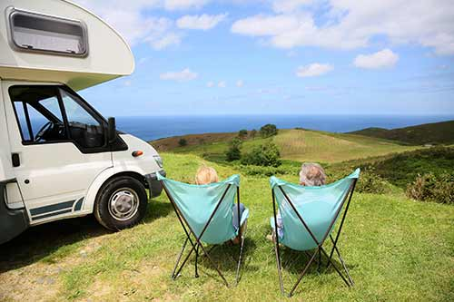 A motorhome, some people and chairs in a campsite by the sea